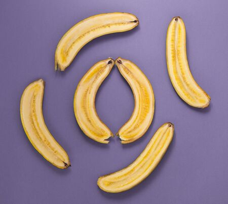 Lots of bananas cut along. Banana halves on a purple background. Ripe fruit.
