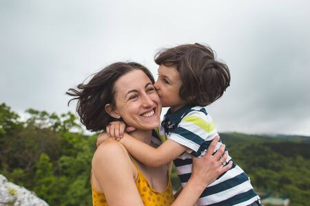 The boy hugs mom. Woman rests with her son in nature. The child kisses mom. Portrait of a mother and baby.
