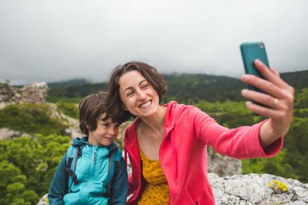 A woman takes a selfie with her son on top of a mountain. The boy is photographed with his mother. Traveling with children. A child walks in the park with his mother.