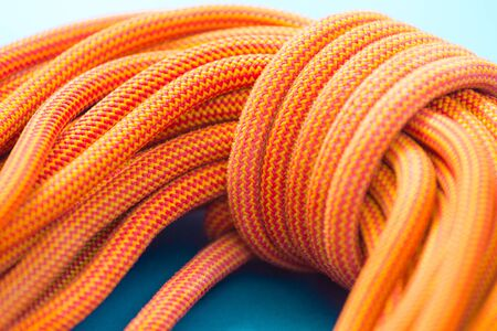 Bayed rope for climbing. Orange rope for mountaineering close up. Node