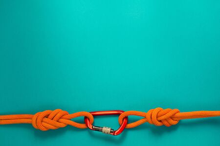 Red carbine with clutch. Equipment for climbing and mountaineering. Safety rope. Knot eight.