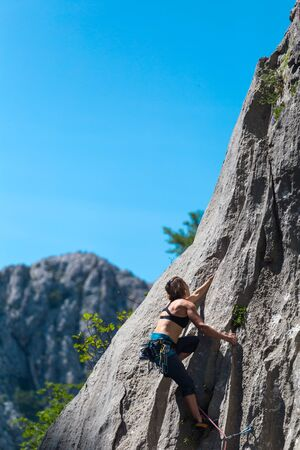 Rock climbing and mountaineering in the Paklenica National Park. A woman overcomes a challenging climbing route on natural terrain. Climber trains on the rocks of Croatia.