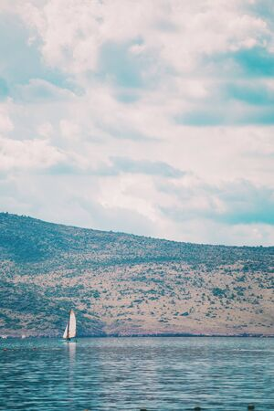 Mountains and the sea. Adriatic coast of Croatia. A yacht against the backdrop of a beautiful shore and sky with clouds. Sailboat in the sea.