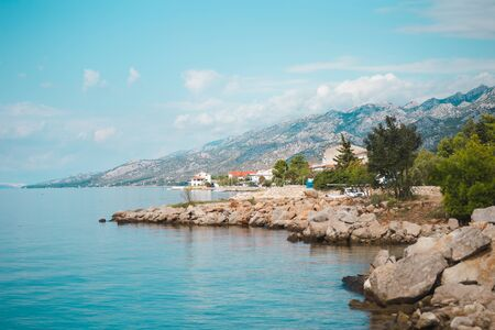 Mountains and the sea. Adriatic coast of Croatia. Town by the sea. Seaside city against the sky with clouds.