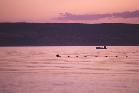 Fishing boat on a background of pink sunset. Sea coast at dawn.