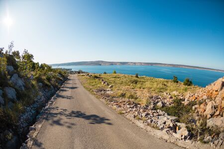 The road along the coast. The path between the mountains and the sea. Asphalt road and picturesque landscape. Stock Photo