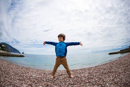The child is resting on the sea. The kid is standing in the sand against the background of the ocean and cloudy sky. A boy is playing on the beach. Stock Photo