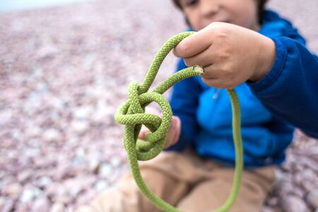 A child learns to knit a knot from a rope. A little boy is trying to tie a knot. Scout training. Childrens hands and safety rope.