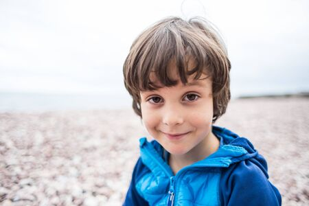 Portrait of a brown-eyed boy. The child is resting on the sea. Toddler is sitting on the sand.
