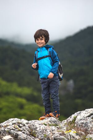 A boy with a backpack stands on top of a mountain. The child climbed to the top. Traveling with children. Active holidays. Stock Photo