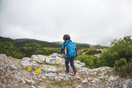 The boy walks along a mountain path. A child with a backpack walks in the woods. Little traveler. Schoolboy on vacation. Traveling with children. Stock Photo