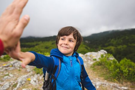 A boy with a backpack climbed to the top of the mountain and gives five. Traveling with children. The child holds out his hand to dad. Kid on the background of cloudy sky. Active lifestyle. Stock Photo