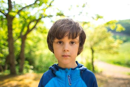 Cute brown-eyed boy. Portrait of a beautiful baby. Child in nature.