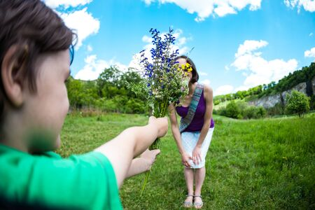 The boy gives his mother a bouquet of wild flowers. A woman is walking with her son in a meadow. A gift for mothers day. The girl takes a bunch of flowers. The child congratulates mom.