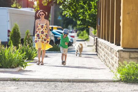 Mom and child are walking along the street. A woman and her son are walking around the city. The boy runs along the sidewalk. Stock Photo