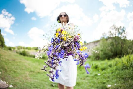 The girl is holding a bouquet of wildflowers. Female hands hold meadow flowers. Walk on the field.