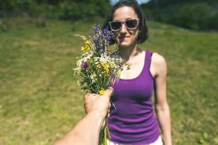 The man holds out a bouquet of wild flowers to the woman. A gift for a girl. The girl is standing in a meadow. Violet flowers in female hands. Date. Stock Photo