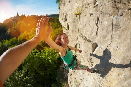The girl climbs the rock. A woman is engaged in fitness in nature. The climber gives five companions after overcoming the climbing route. The joy of achieving the goal. Teamwork. Gesture with hand.