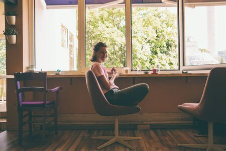 A woman is sitting near the window and drinking coffee. Girl with a phone in her hands. Relax at home. A cozy coffee shop.