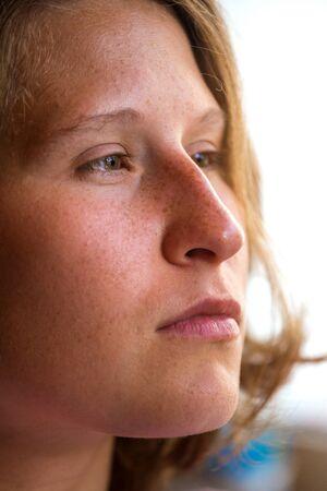 Portrait of a woman near the window. Pensive girl. Sad woman.