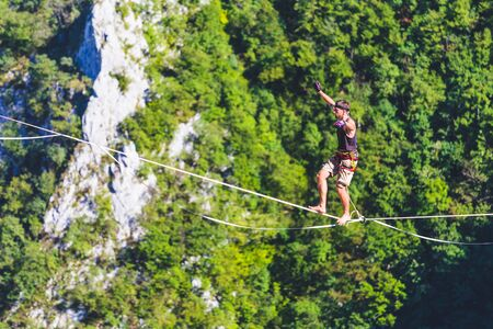 Highline in the mountains. A man goes on a stretched sling. Highliner is on the line. A tightrope walker catches balance. Equilibrium. Confidence in a tense situation.