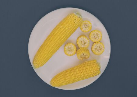 A plate with corn on a turquoise background. Corn slices. Cereal product. A dish of corn.