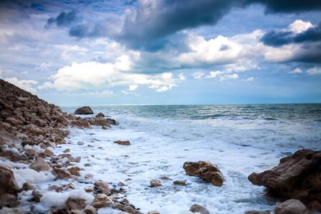 Rocky seashore. Strong waves and wind. Storm. Ocean against the background of the cloudy sky. Big stones on the seashore. Stock Photo