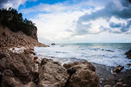 Rocky seashore. Strong waves and wind. Storm. Ocean against the background of the cloudy sky. Big stones on the seashore. Stock fotó