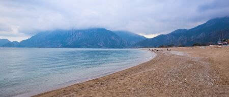 Sea on a cloudy day. Turkish beach in a rainy day. Storm clouds. Sandy beach on a background of high mountains.
