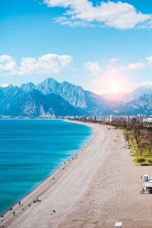 Turkish beach without people. Mediterranean Sea in Turkey. Ocean waves and coastal sand. Resort on the background of mountains and sky. Deserted beach. Stock Photo