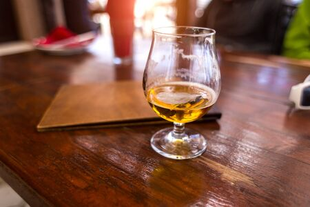 A glass of beer at the bar. Half-empty glass with an alcoholic drink. Wineglass. Light beer. Drunk drink. Stock Photo