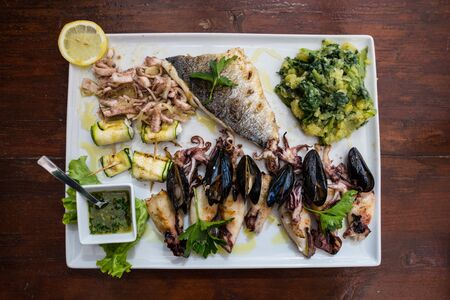 Seafood plate. Fish restaurant. Mediterranean Kitchen. Squids, mussels and octopus with grilled vegetables and sauce. The menu is a Croatian restaurant. Stock Photo