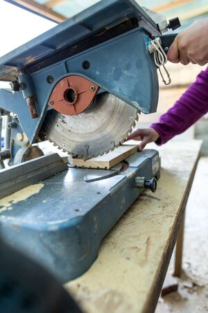 A woman works in a carpentry workshop. The girl handles the wood. Woman in the male profession. Feminism. The girl learns to work with carpentry tools. Female hands closeup. A circular saw.