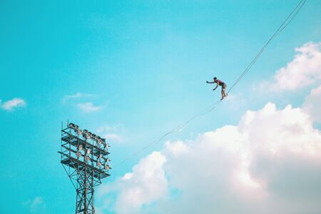 Highliner on the background of blue sky makes a move. A man is walking along a stretched sling. Performance tightrope walker. Man balances over the abyss. A decisive step forward. Foto de archivo