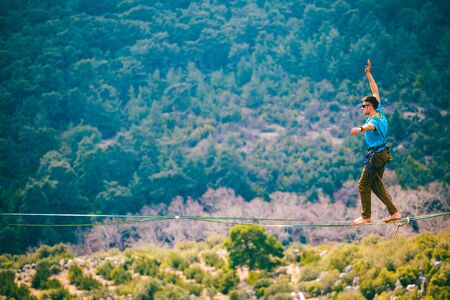 A man is walking along a stretched sling. Highline in the mountains. Man catches balance. Performance of a tightrope walker in nature. Highliner on the background of the mountains. Stock Photo