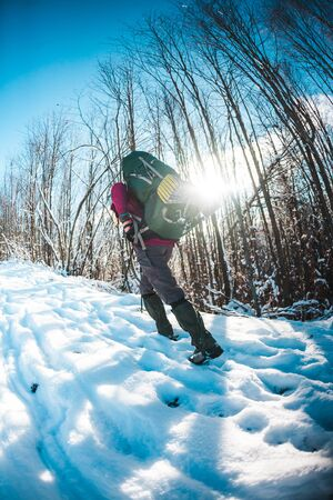 Woman with backpack and snowshoes in the winter mountains. Travel to scenic places. Portrait of a blonde with trekking sticks. A tourist walks through a snowy forest. Girl walks along the path.