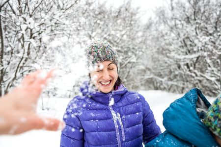 The girl plays snowballs. Emotional woman having fun with friends in a winter park. Walk through the snowy forest. Winter fun. Stock Photo