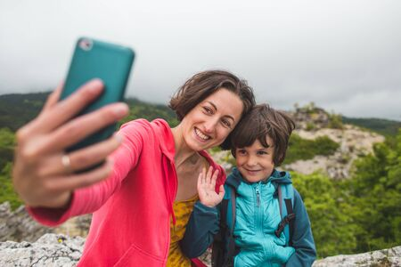 A woman takes a selfie with her son on top of a mountain. The boy is photographed with his mother. Traveling with children. A child walks in the park with his mother. Zdjęcie Seryjne - 133814647
