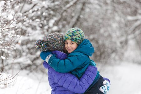 The kid hugs Mom. A boy with his mother on a winter walk. A child in a knitted hat kisses his mother. The woman supports her son. Motherhood. The family spends time together. Family values. Zdjęcie Seryjne - 133815908