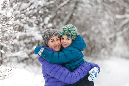 The kid hugs Mom. A boy with his mother on a winter walk. A child in a knitted hat kisses his mother. The woman supports her son. Motherhood. The family spends time together. Family values. Zdjęcie Seryjne - 133815910