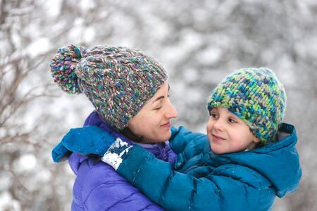 The kid hugs Mom. A boy with his mother on a winter walk. A child in a knitted hat kisses his mother. The woman supports her son. Motherhood. The family spends time together. Family values.