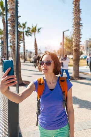 A girl takes a selfie on the waterfront. A woman walks through the resort town and takes pictures. Brunette travels around the Turkish city.