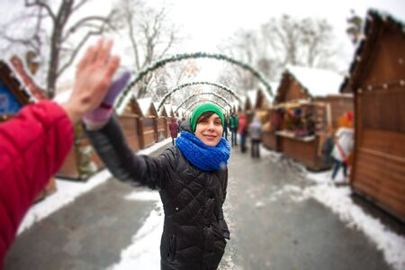 Woman traveling to European cities. The girl gives five to a friend. Sights of a beautiful Ukrainian city. Tourist on a snowy street. Winter holidays. Walk through the decorated city. Christmas. Banco de Imagens
