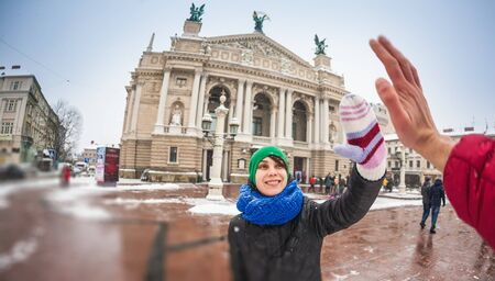 Woman traveling to European cities. The girl gives five to a friend. Tourist on the background of the Lviv National Theater of Opera and Ballet. Sights of a beautiful Ukrainian city. Winter holidays.