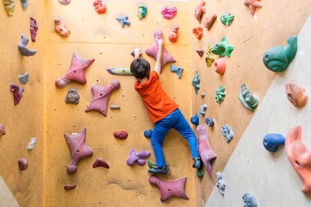 boy is training on artificial boulders in the gym, bouldering. Extreme sports. A child climbs on a children's climbing wall.