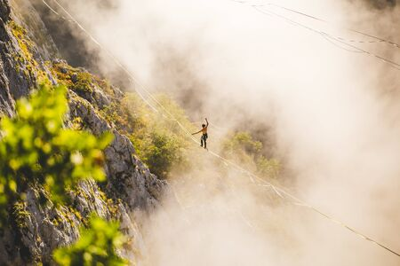 a man walks along a stretched sling high above the clouds. highliner catches the balance on a long and high sling pull in a canyon. Extreme sports in Bosnia and Herzagovina,