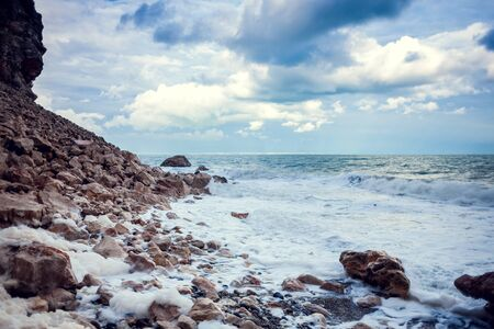 Rocky seashore. Strong waves and wind. Storm. Ocean against the background of the cloudy sky. Big stones on the seashore.