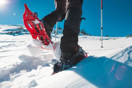 Een man in sneeuwschoenen. Uitrusting voor winterwandelingen in de bergen. Voeten op de sneeuw close-up. Actieve levensstijl. Reis in de bergen in de winter. Extreme vakantie in de natuur.
