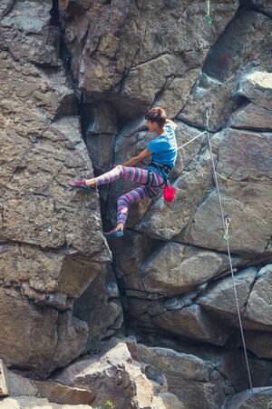 The girl climbs the granite rock. Rock climber trains on natural terrain. Extreme hobby. 스톡 콘텐츠
