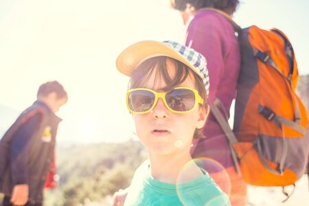 Portrait of a boy in sunglasses. A woman with two children. The boy walks with his mother and brother. Family holiday. Brunette with a backpack travels with children. Mom holds sons hands. Stock Photo - 136727967